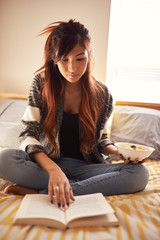 teen asian girl reading and eating soup in bedroom
