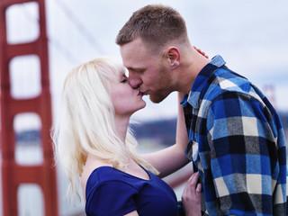 romantic couple kissing in front of golden gate bridge