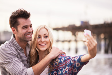 cute couple taking selfies together on beach