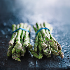 fresh asparagus in two bunchess on slate with copy space
