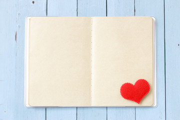 Notebook and heart decoration on blue wooden table