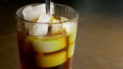 Fresh brewed coffee pouring into glass of ice
