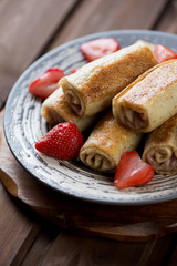 Close-up of rolled crepes with strawberry stuffing, studio shot