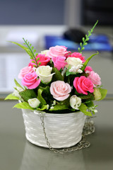 Artificial roses in a vase of flowers.