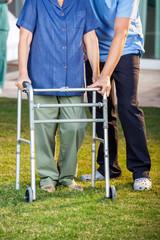 Caretaker Helping Senior Woman In Using Walking Frame