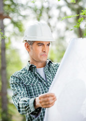 Male Architect Analyzing Blueprint At Site