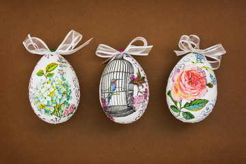Three decorated Easter eggs on the brown paper