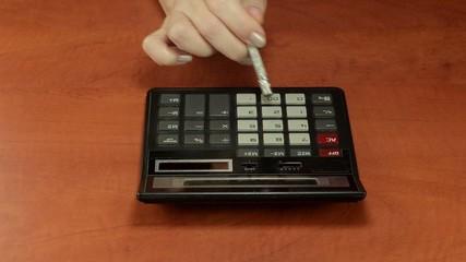 Pencil eraser pushing a calculator buttons