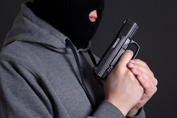 masked man criminal holding gun over grey