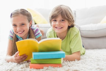 Happy siblings reding book while lying on rug