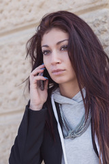Young woman portrait talking at the phone in a park. Filtered im