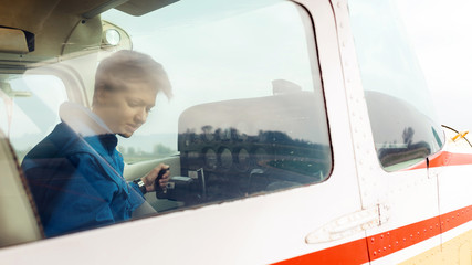 Young woman airplane pilot, view through the window.