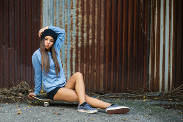 Full body teenager portrait with skateboard against old grunge r