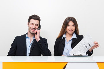 Young man and woman at work as receptionist in hospital talking