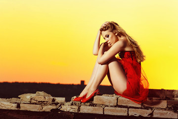 A depressed sexy girl in red dress is sitting at bright dawn bac