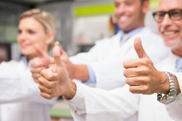 Positive co-workers standing with thumbs up