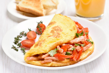 Egg omelette with vegetables and ham on white plate
