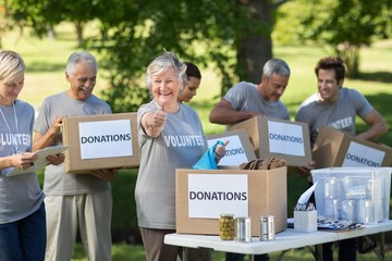 Happy family holding donations boxes with thumb up