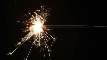 A burning sparkler against black background