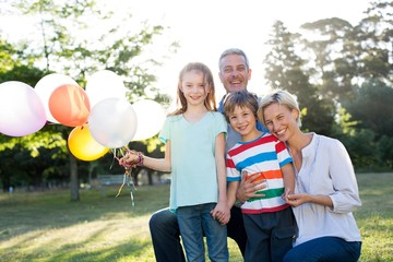 Happy family holding balloons at the park