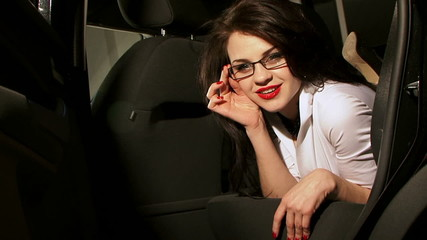 Sexy Young Lady Lying On Backseat of Black Modern Car
