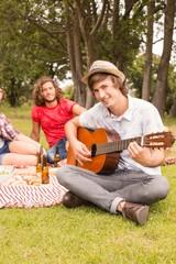 Happy friends in the park having picnic