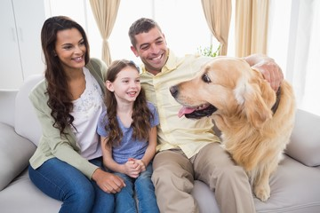 Family looking at Golden Retriever on sofa