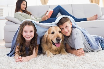Happy siblings with dog under blanket