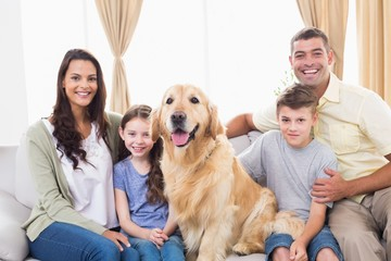 Happy family sitting with Golden Retriever on sofa