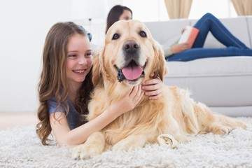 Girl embracing Golden Retriever while lying on rug