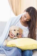 Woman playing with cute puppy on sofa