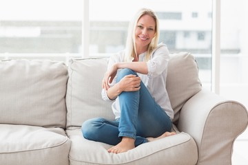 Portrait of happy woman sitting on sofa