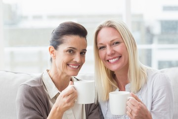 Smiling female friends having coffee in living room