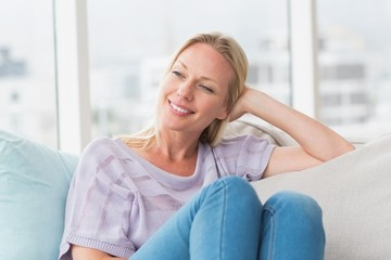 Relaxed woman looking away while sitting on sofa