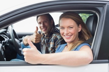 Couple smiling at the camera with thumbs up