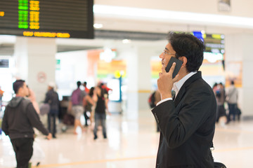 Asian Businessman on the phone during his business travel, at th