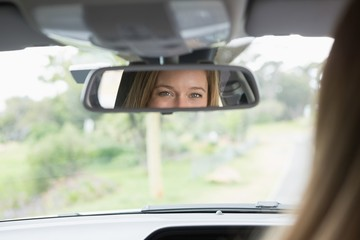 Young woman in the drivers seat looking in the mirror