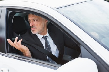 Perplexed businessman in the drivers seat