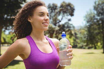 Fit woman holding bottle of water