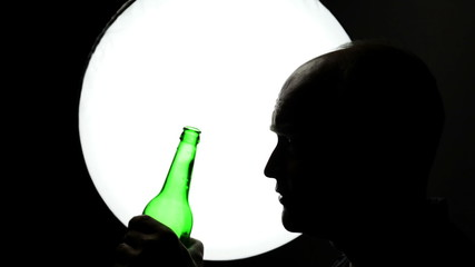 Middle-aged man is drinking alcohol - backlit