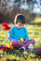Adorable boy in the park, having fun with colored eggs for Easte