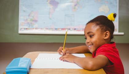 Cute little girl writing book in classroom