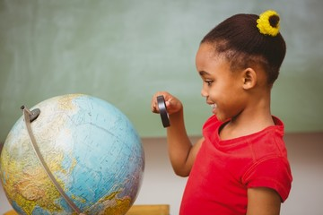 Girl looking at globe through magnifying glass