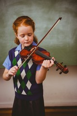 Cute little girl playing violin in classroom
