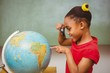 Little girl looking at globe through magnifying glass