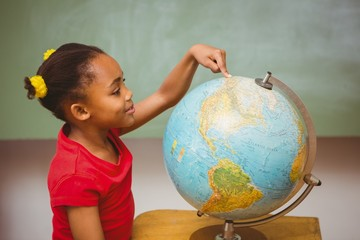 Little girl pointing at globe in classroom
