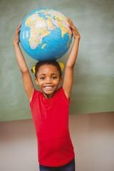 Little girl holding globe over head