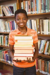 Portrait of cute boy carrying books in library
