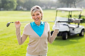 Cheerful golfer standing on the putting green