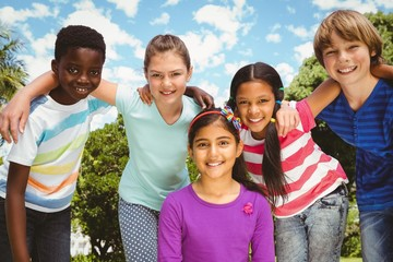 Happy children forming huddle at park